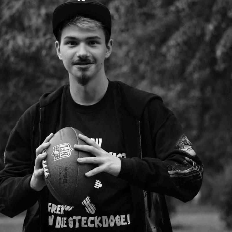 Mann hält Football und ist zum werfen bereit.