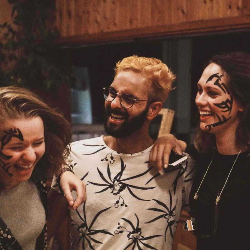 Drei junge Menschen lachen und umarmen sich.