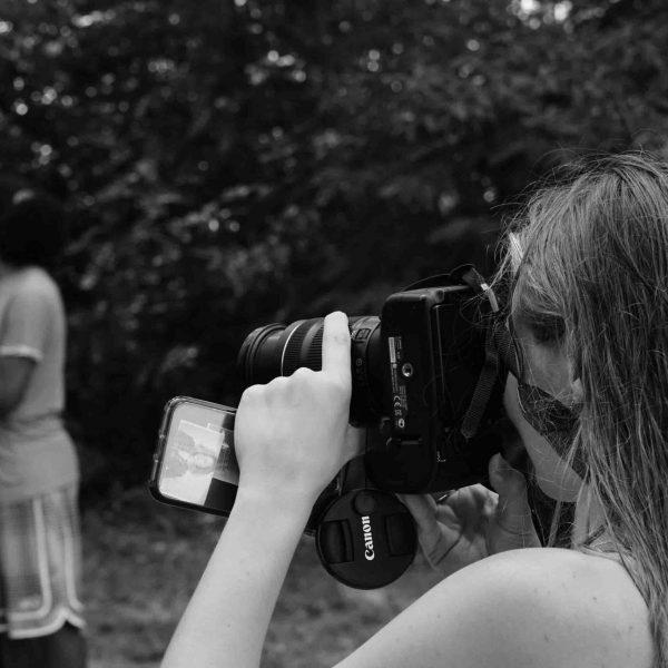 Frau mit Kamera macht Fotos einer Gruppe.