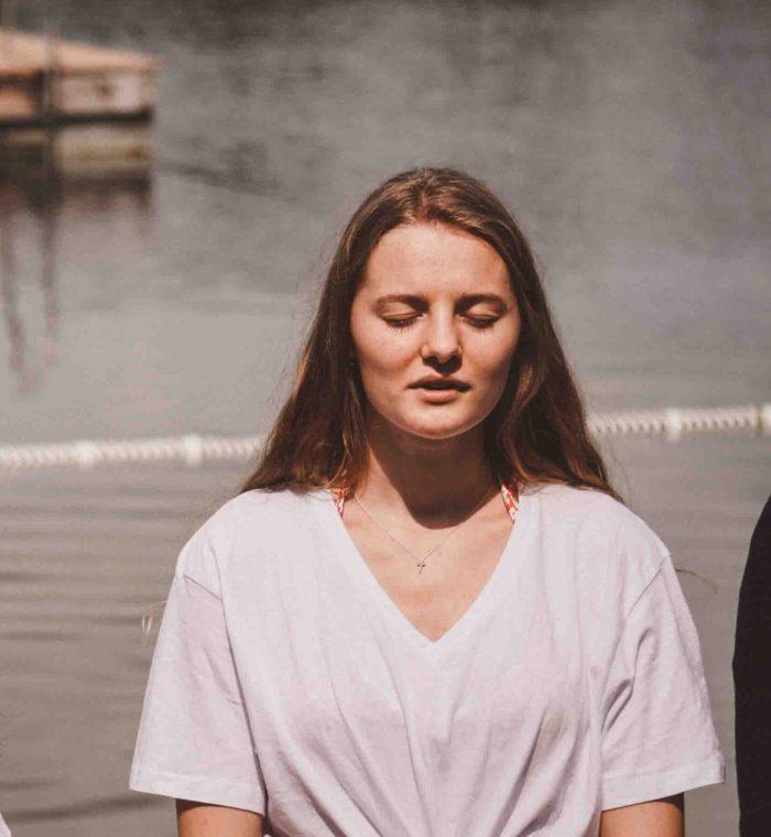 Frau steht mit geschlossenen Augen im See bei Taufe.