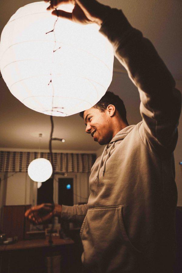 Mann hängt eine Lichterkette auf.