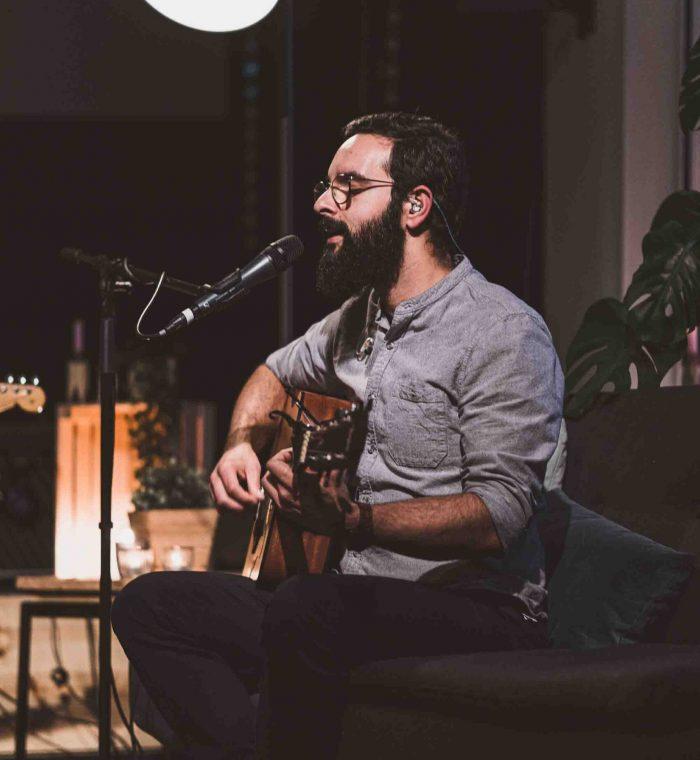Singender, junger Mann mit Gitarre auf Couch.