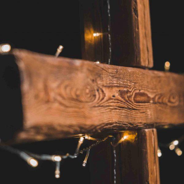 Mit Lichterkette geschmücktes Kreuz aus Holz.