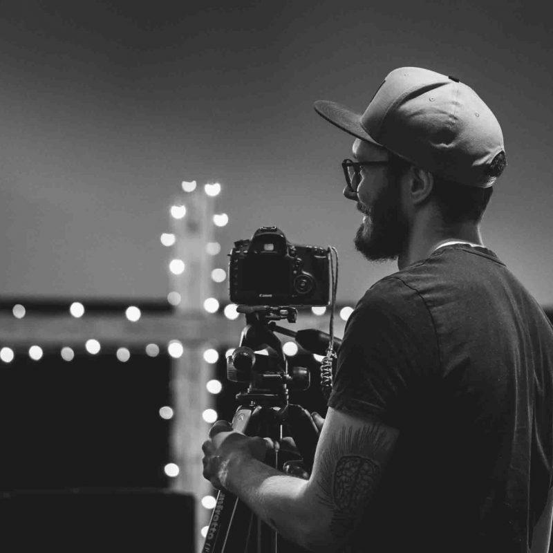 Kameramann mit Cap filmt bei Videodreh.