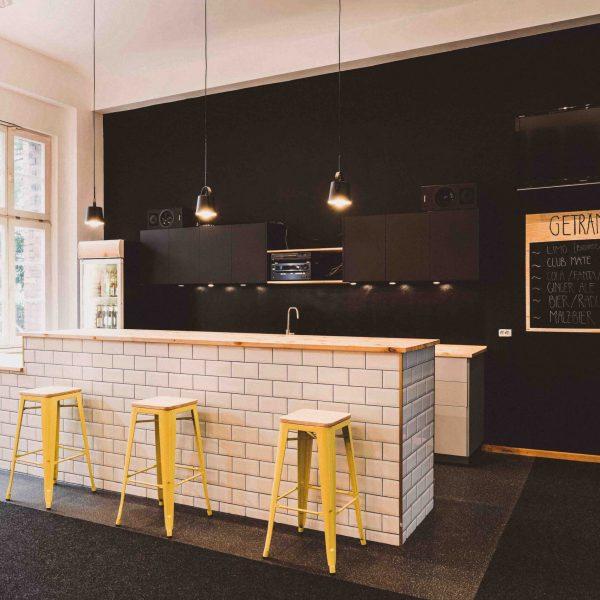 Barbereich in den Gemeinderäume mit gefliester Theke und Hängelampen.