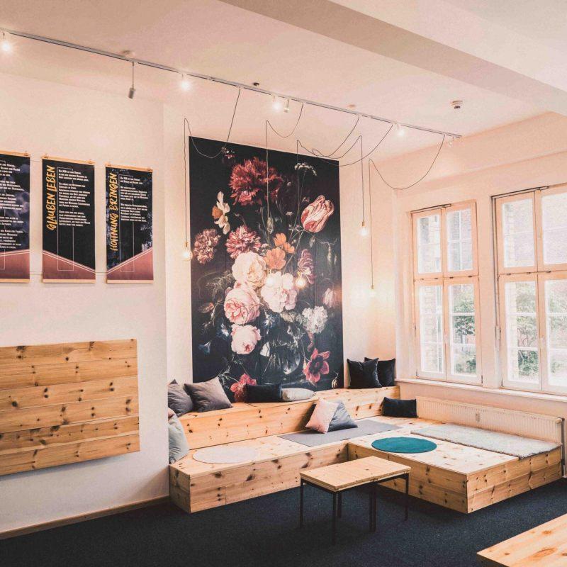 Foyer der Gemeinderäume mit Holzplattform zum sitzen und großem Wandbild.