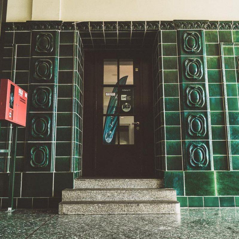 Tür zu den Gemeinderäumen im grün gefliessten Foyer.