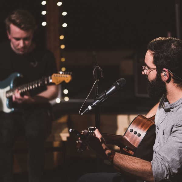 Zwei Männer mit Gitarren die Lobpreis machen.
